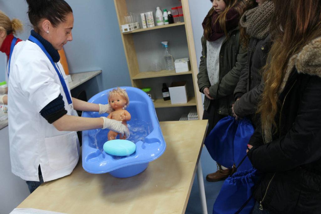 Práctica auxiliar de enfermería en pediatría bañando a un muñeco bebé
