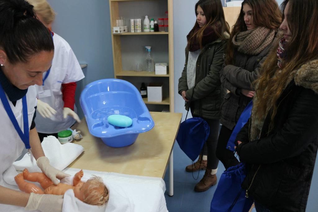 Práctica auxiliar de enfermería en pediatría secando a un muñeco bebé