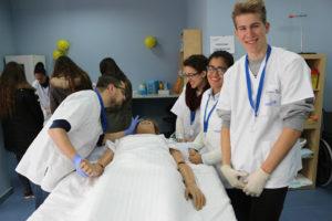 Alumnos en practica de auxiliar de enfermería con muñeco encamado