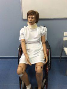 Práctica de auxiliar de enfermería con muñeco en silla de ruedas