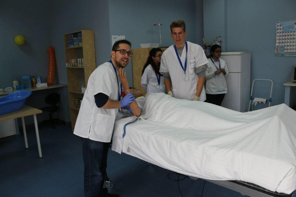Alumnos de auxiliar de enfermería realizando práctica con muñeco